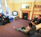 Friends talking in plymouth student house lounge on sofas.
