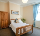 Large double bedroom with wooden furniture in plymouth uni house.