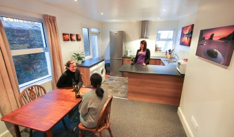 Plymouth university student housemates talking in modern kitchen.